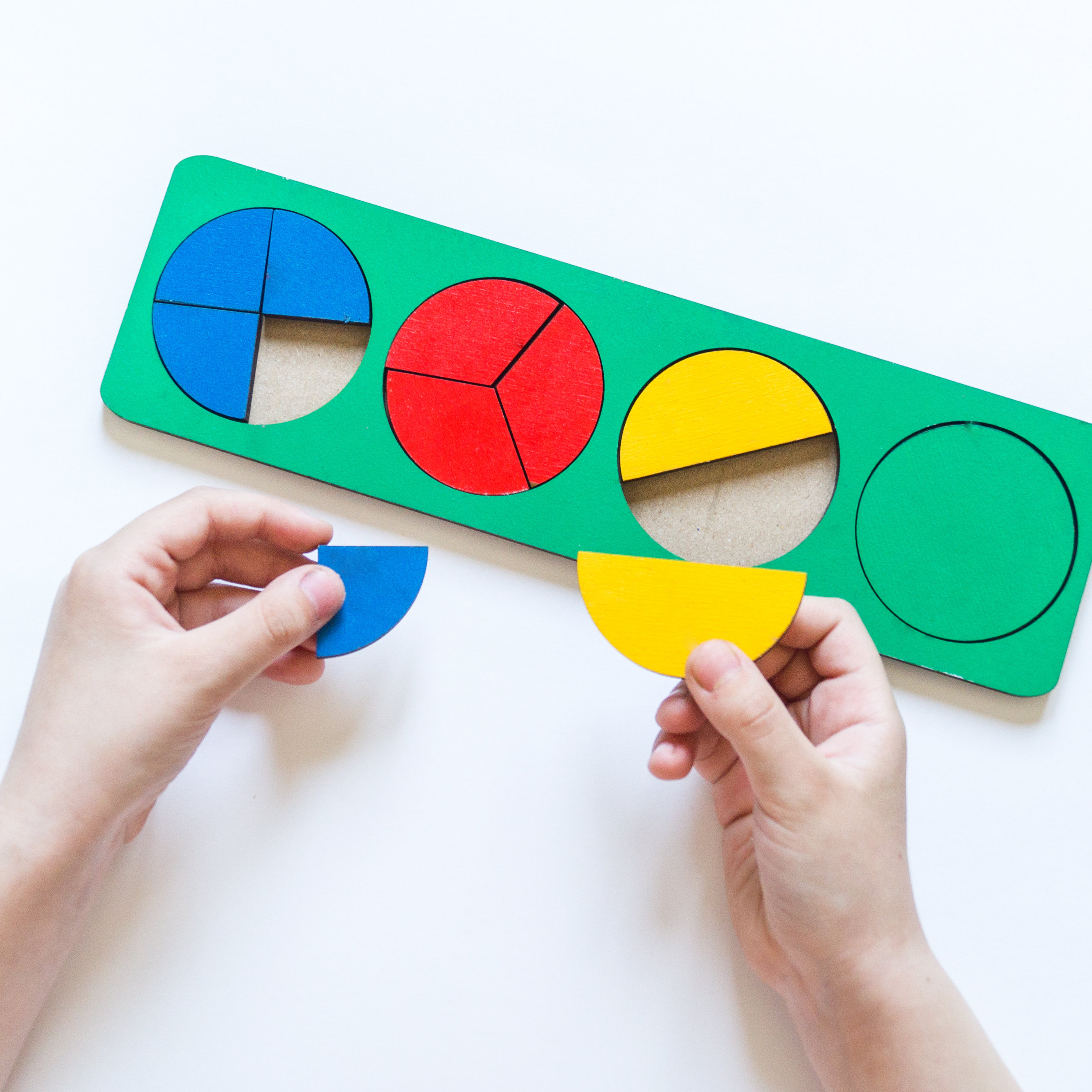 Child playing with circle fractions puzzle.